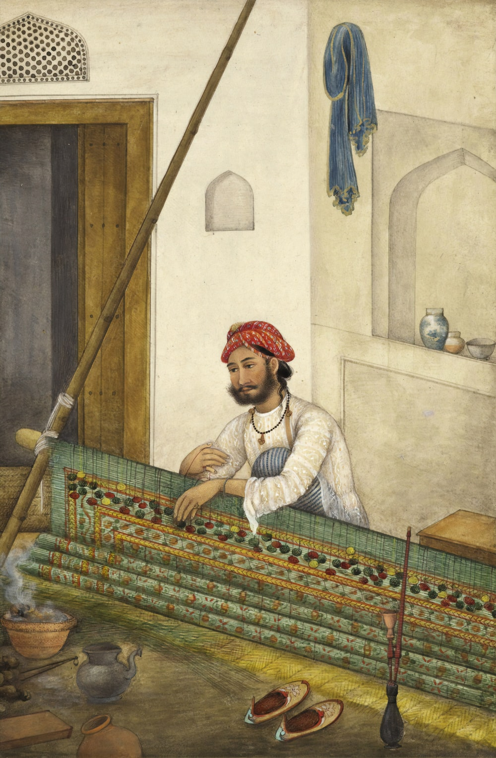 man sitting beside wall painting