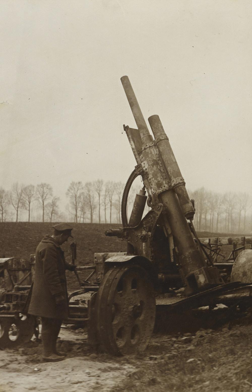 man standing beside towed artillery
