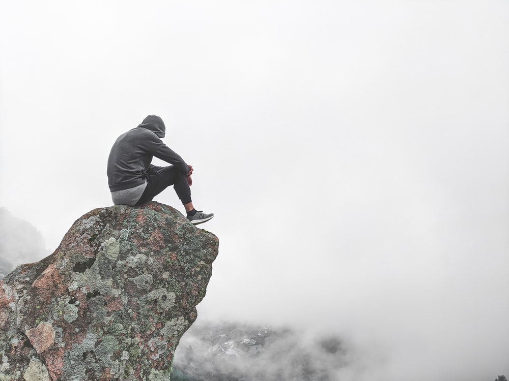 person in gray hoodie standing on rock