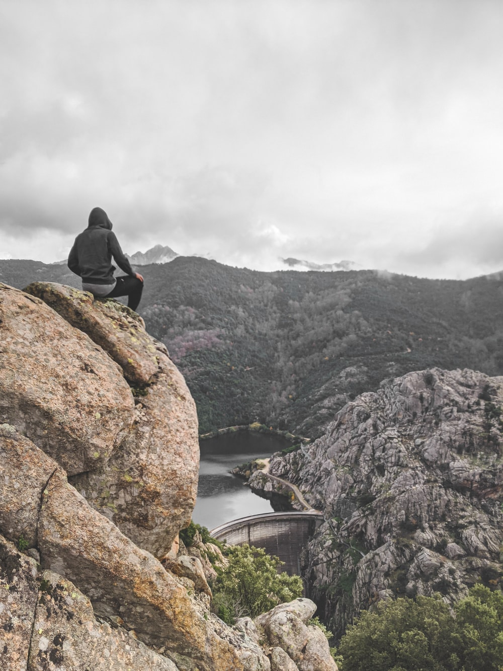 person wearing gray pullover sitting on mountain edge