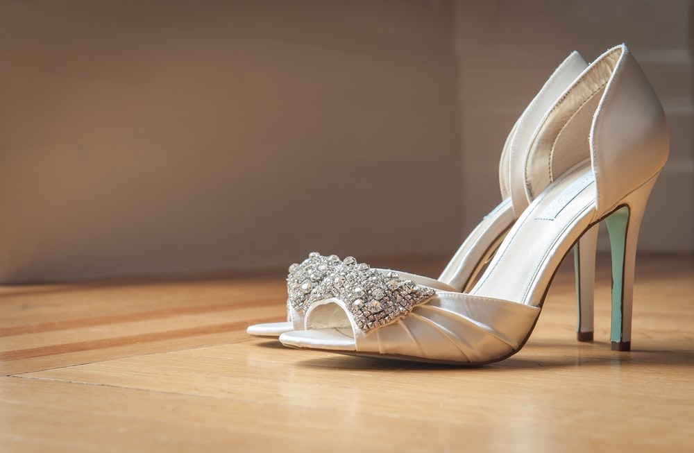 pair of silver open-toe stilettos on brown surface