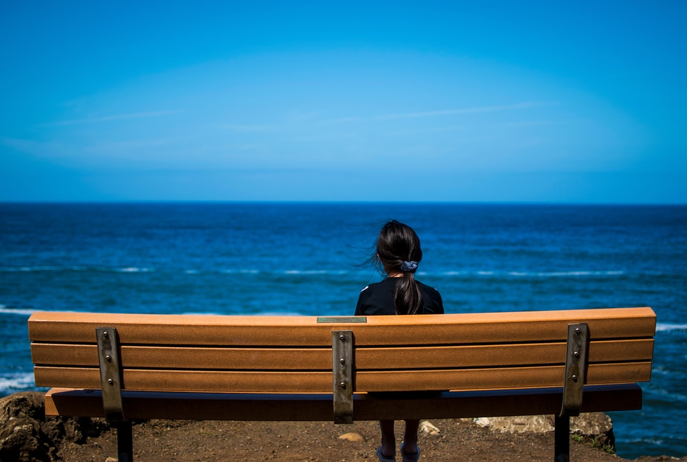 woman wearing black top sitting on brown bench chair