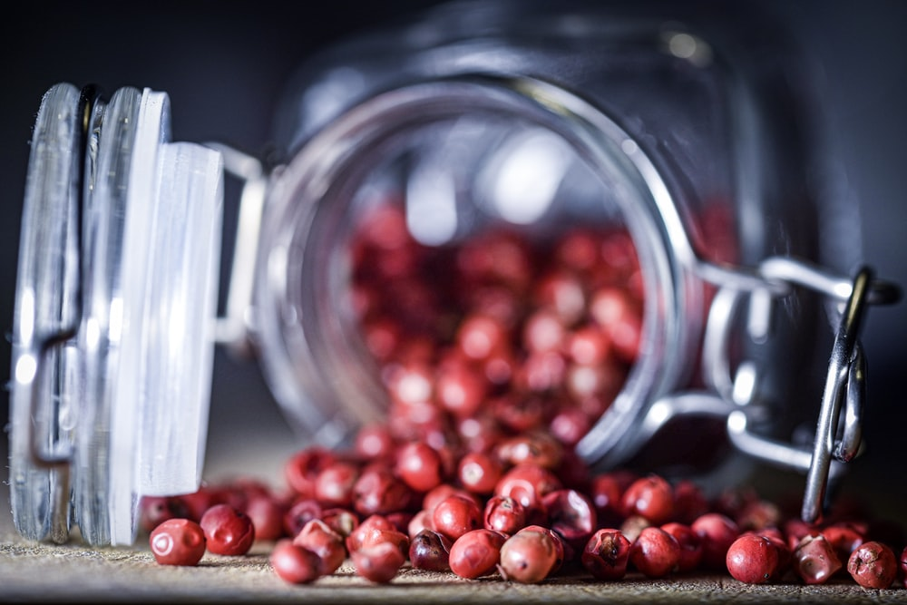 macro photography of red fruit lot in jar