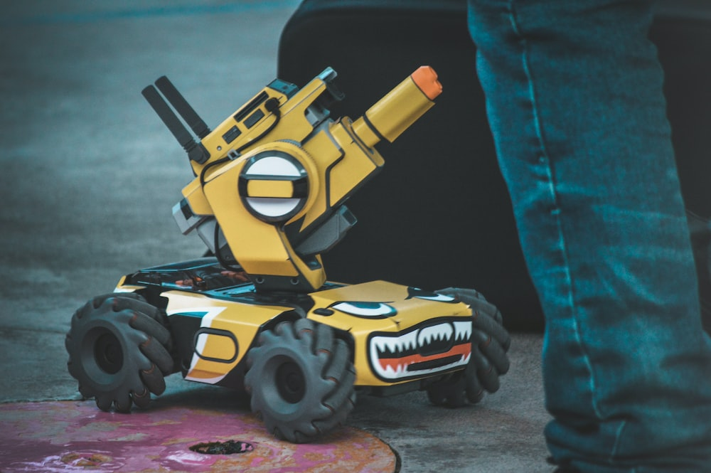 yellow and black 4-wheeled robot vehicle toy