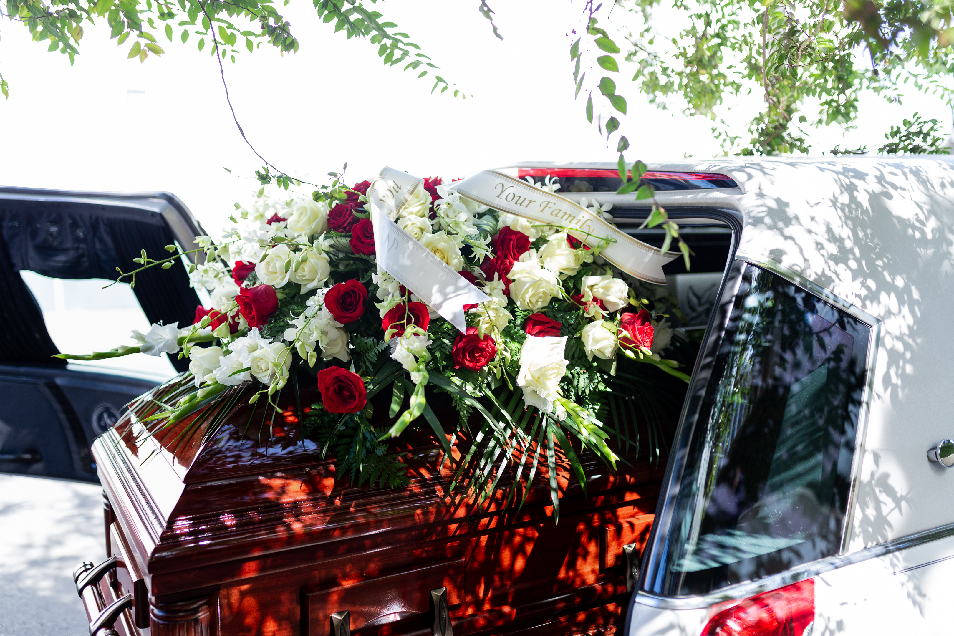 funeral details of flowers on cherry wood casket and white car