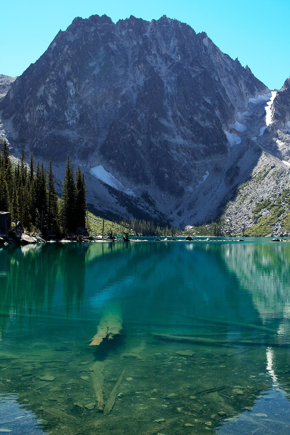 calm body of water overlooking snow capped mountains