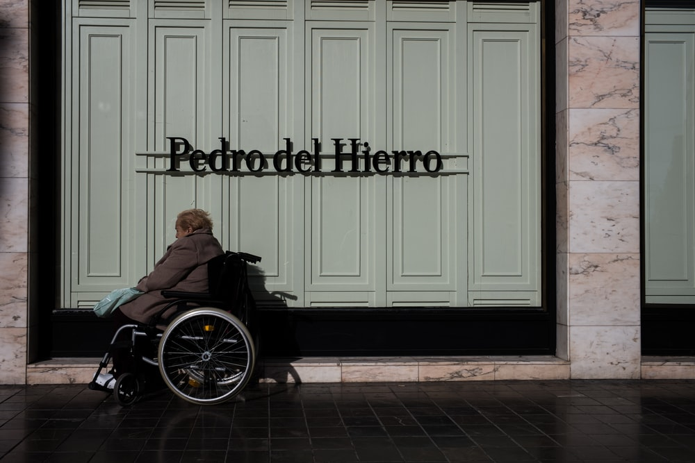 person on black wheelchair beside wall