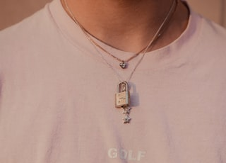 person wearing silver-colored necklace and white crew-neck top