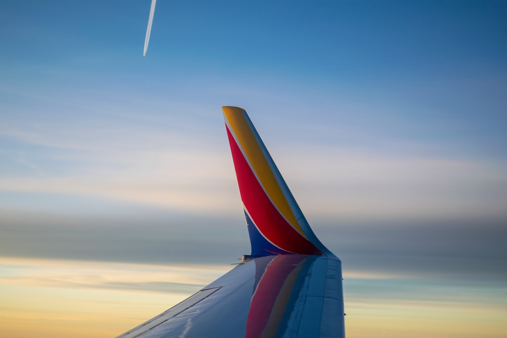 white, yellow, red, and blue passenger plane wing