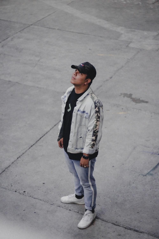 man standing on grey pavement