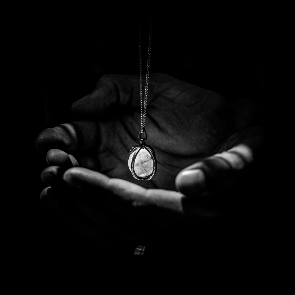 greyscape photography of pendant necklace on human hand