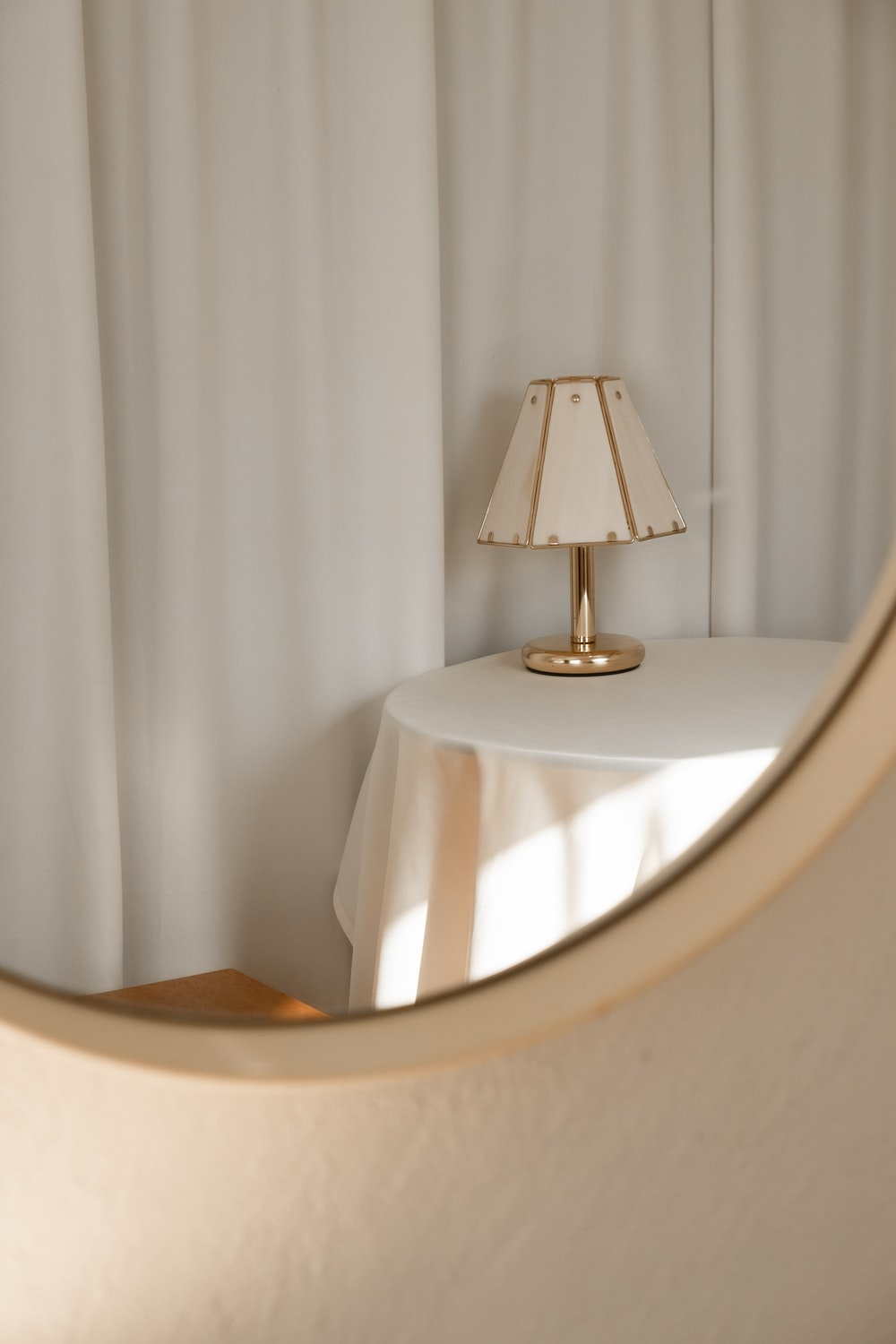 white and gold table lamp on whtie round table