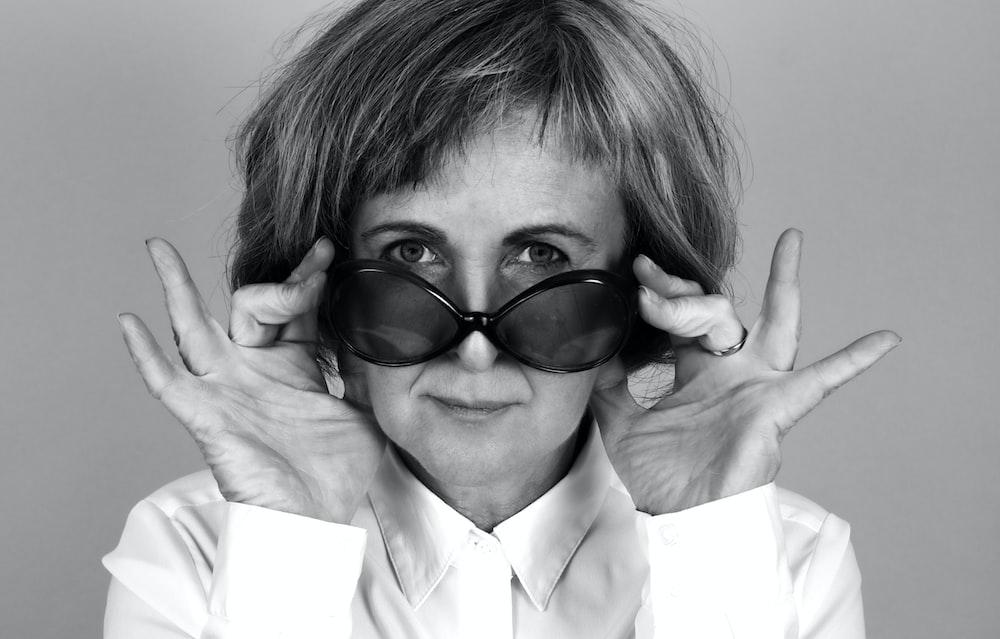 woman holding sunglasses grayscale photo