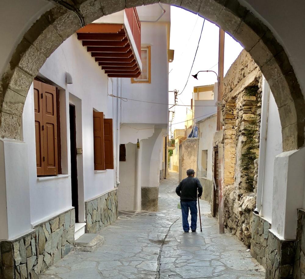 man walking near white concrete building