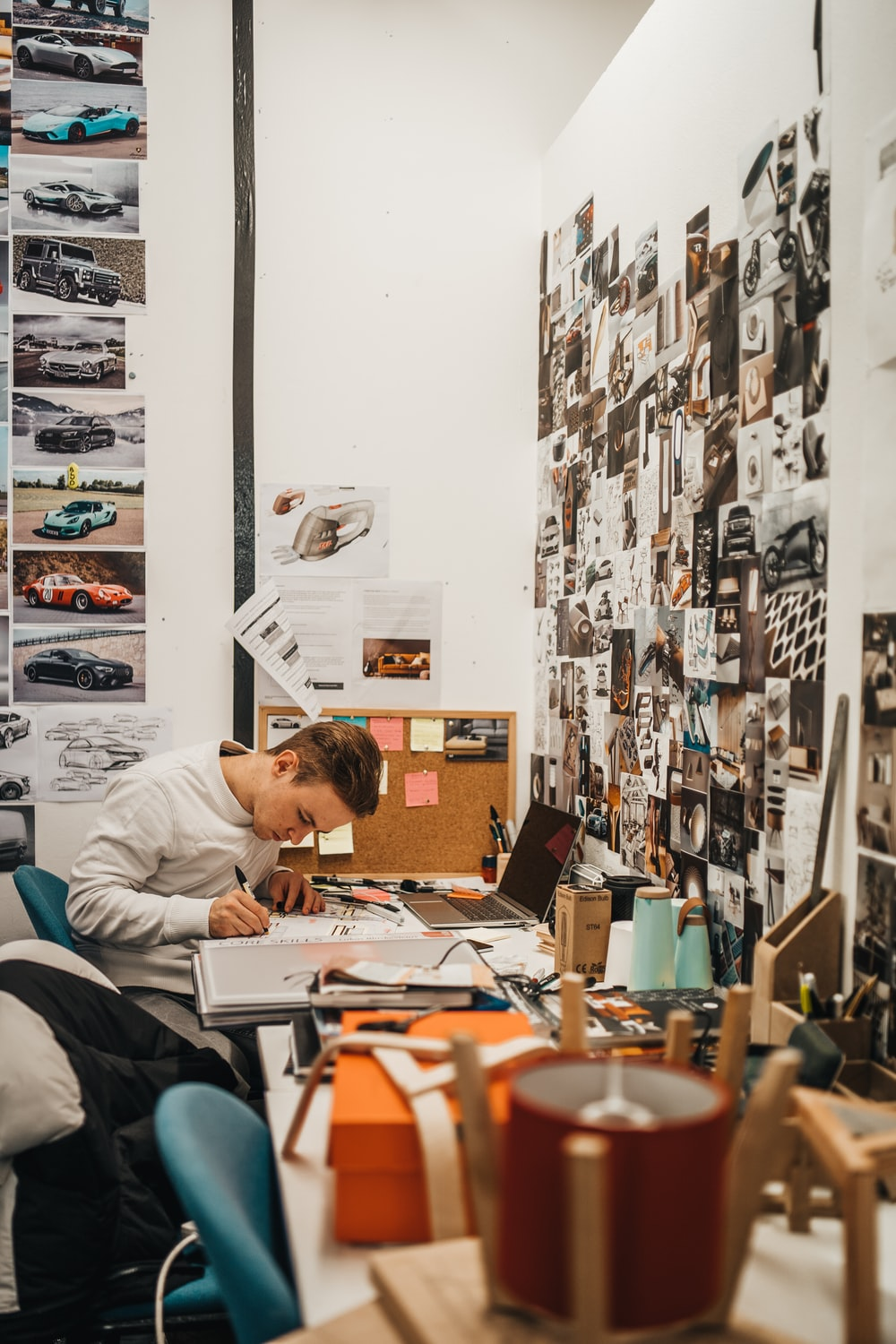 man writing beside wall with car photos