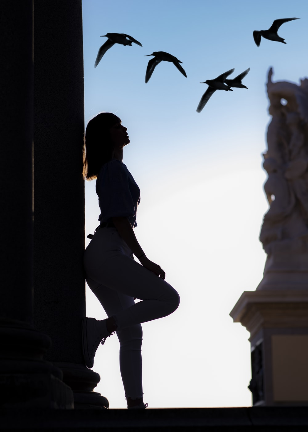 silhouette of woman laying on pillar