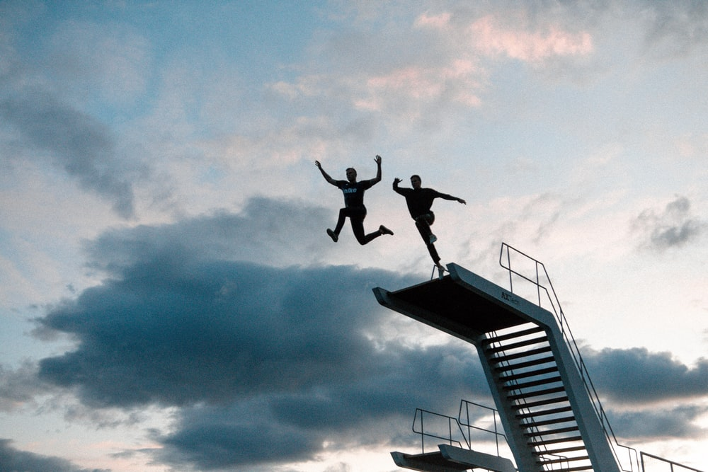 two person about to jump of swimming pool diving board