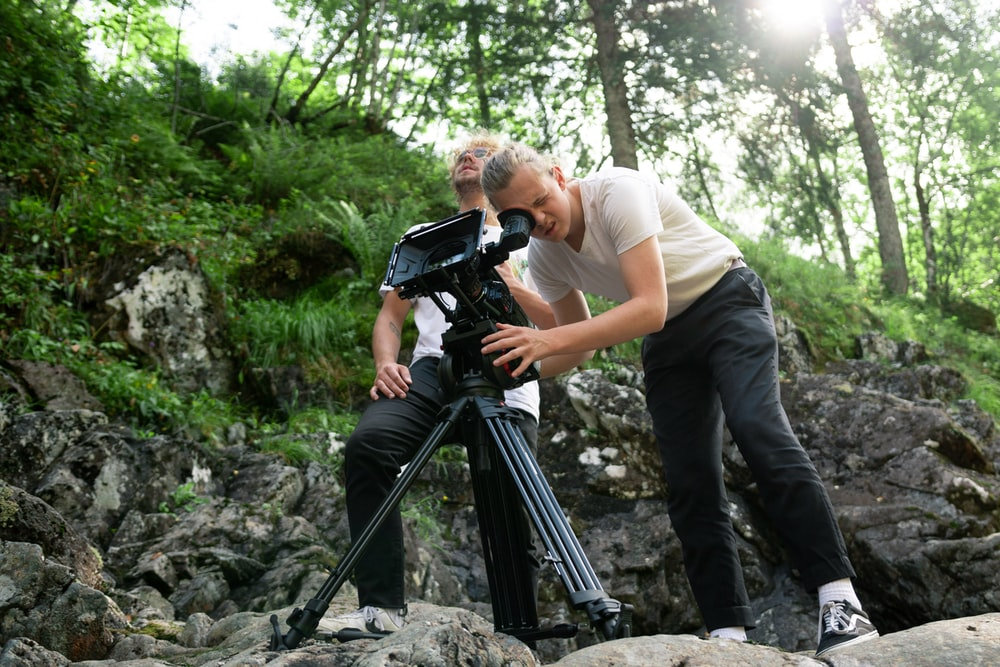 two men doing video recording while standing on rocks