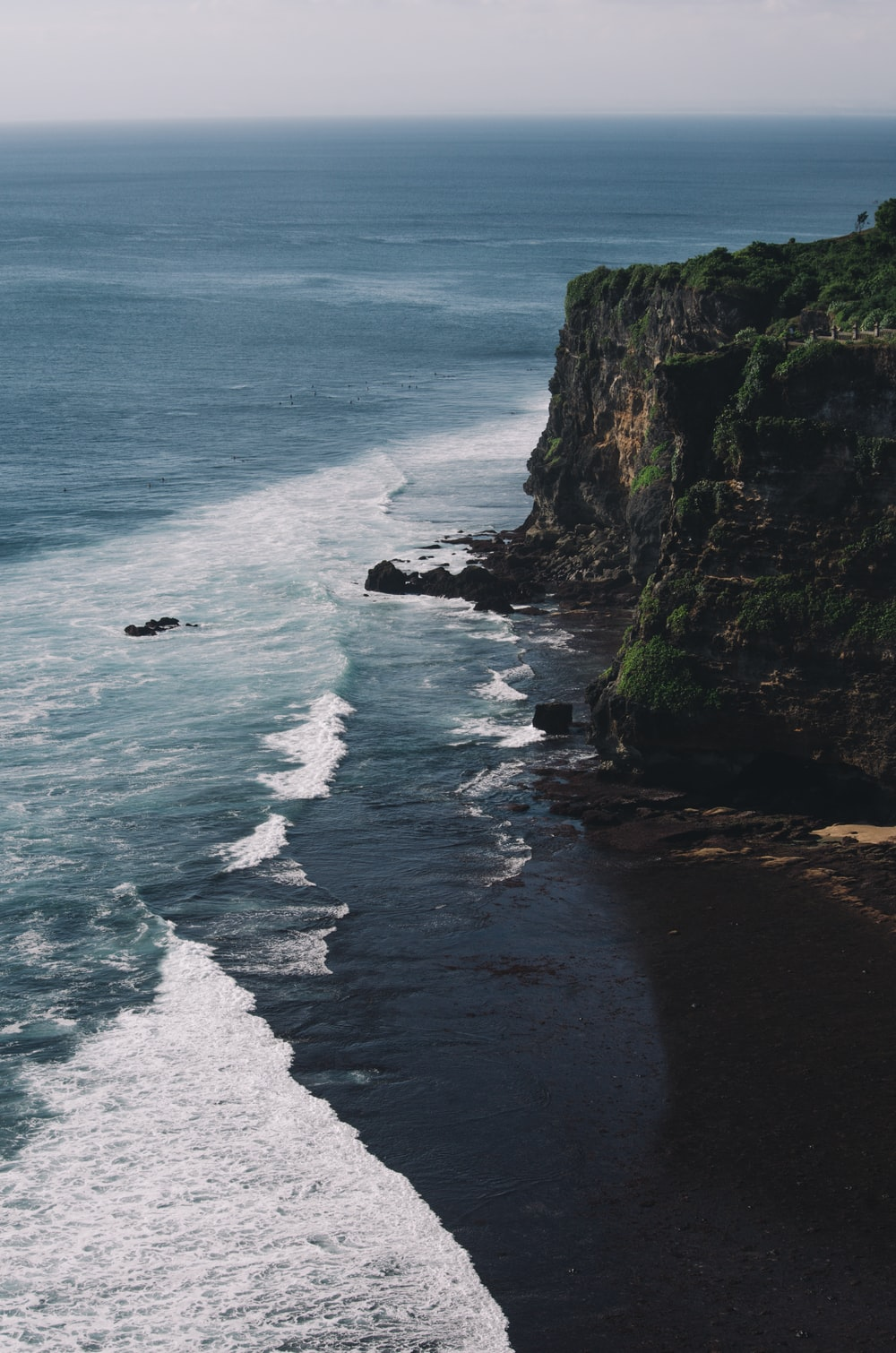 aerial photography of cliff beside body of water during daytime