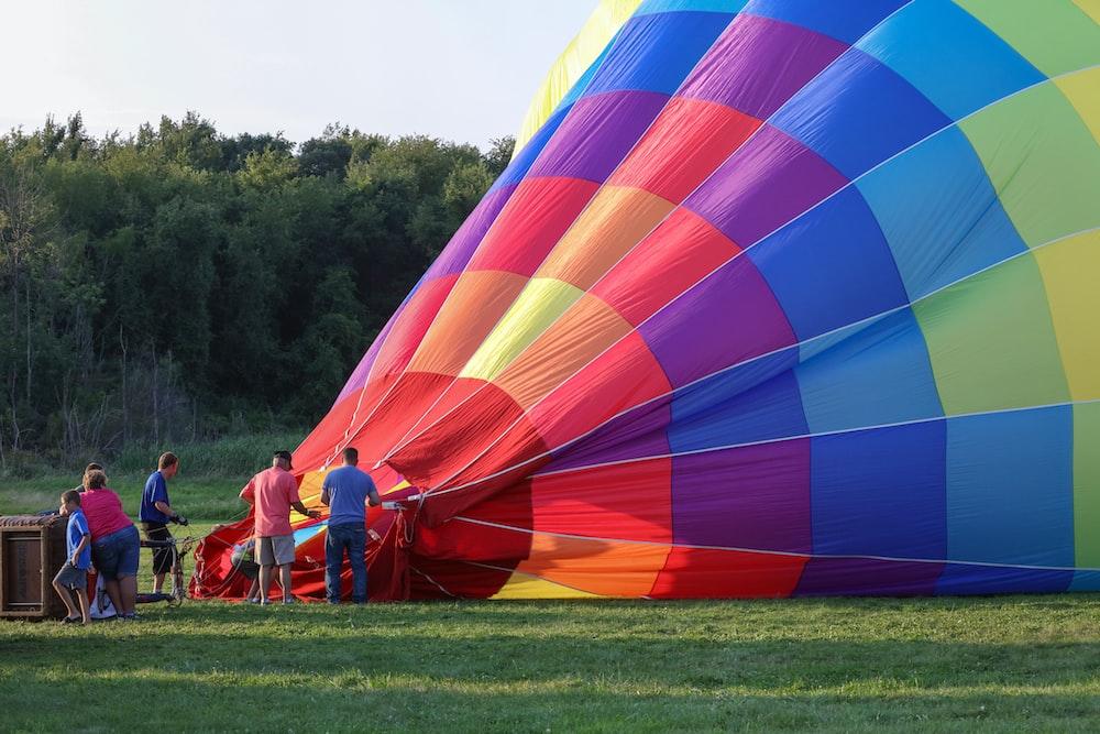 five person standing beside hot air balloon