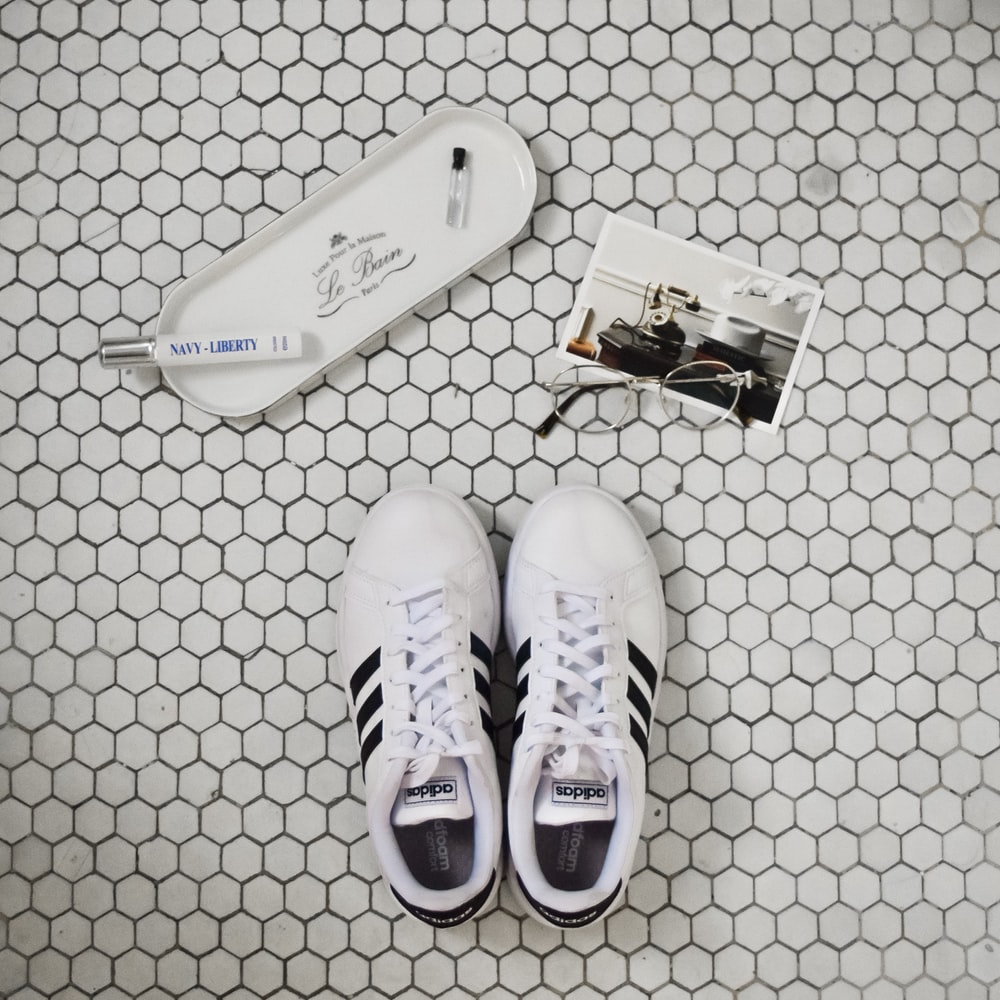 pair of white-and-black Adidas Superstar sneakers