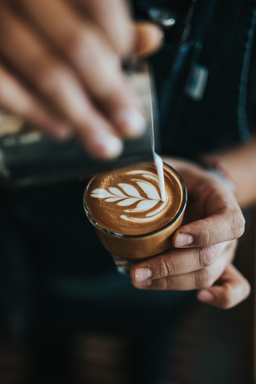 person pouring cream on coffee