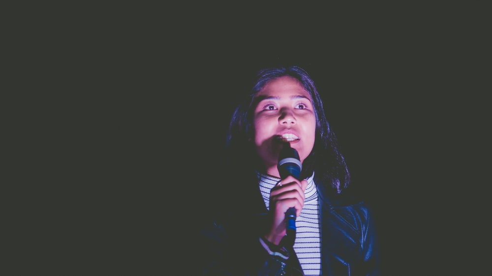low-light photo of woman holding black microphone