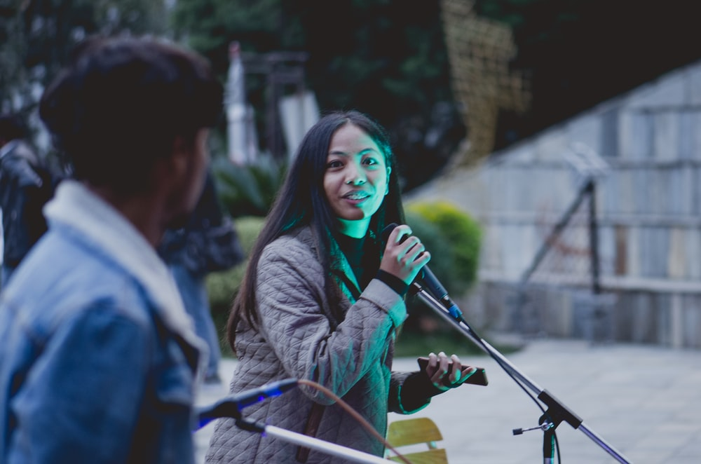 selective focus photo of woman holding microphone