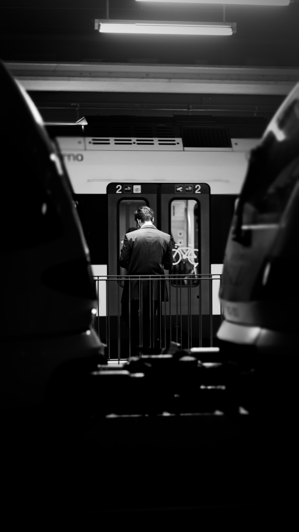 gray-scale photo of man entering train