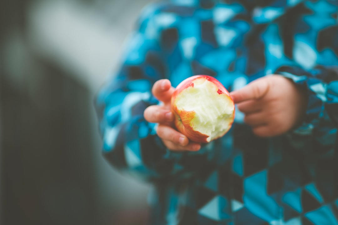 Young boy with bitten apple