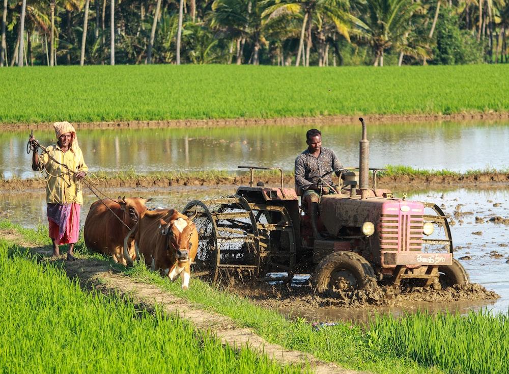 man riding farm equipment during daytime