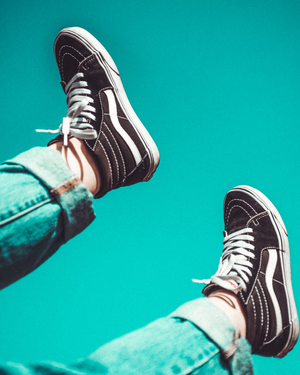 person wearing black-and-white Vans Sk8-Hi sneakers
