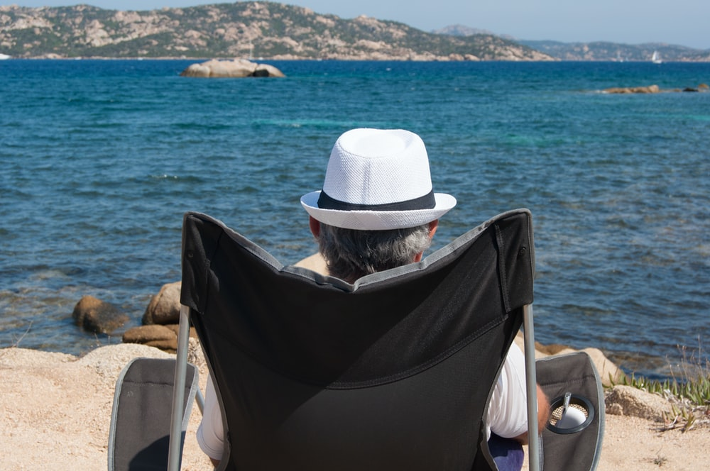 man wearing white fedora hat sitting on gray wheelchair