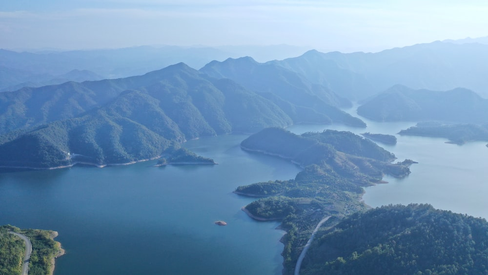 aerial photography of body of water viewing mountain under blue and white sky