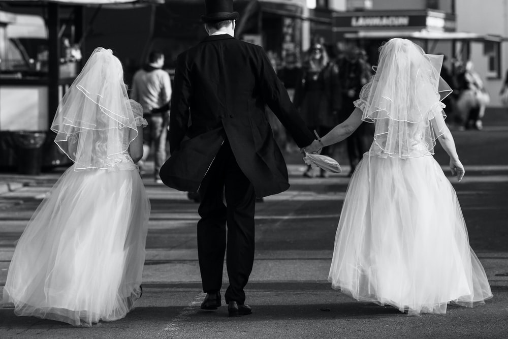 grayscale photography of two brides and groom walking on road