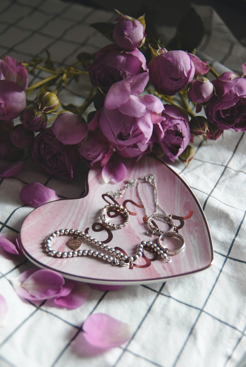silver-colored rings and bracelet on plate with pink roses