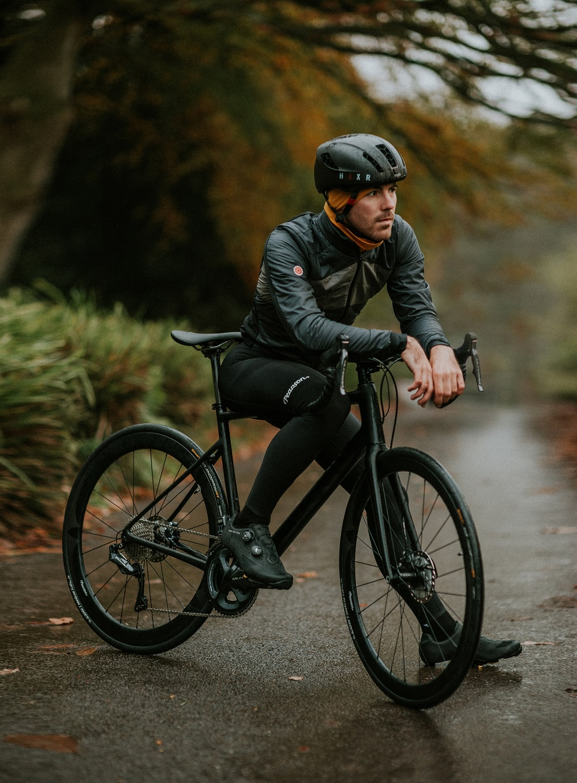 man sitting on road bike near trees