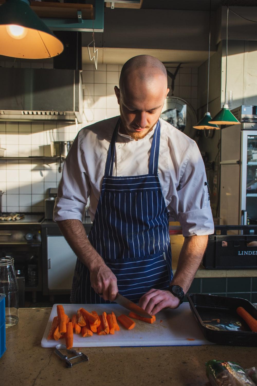 man slicing orange carrots