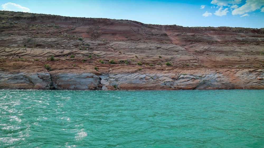 brown rock formation near sea water
