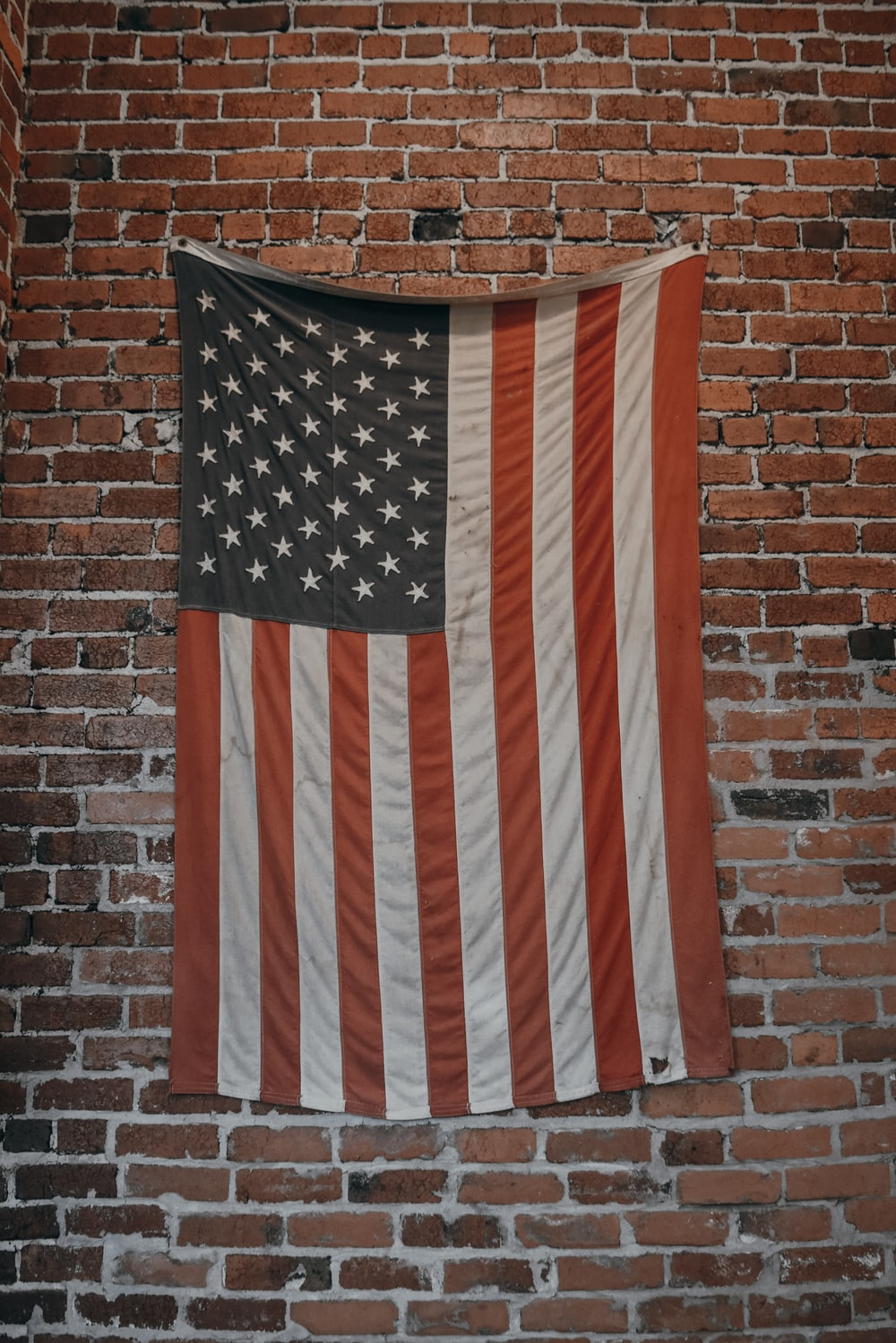 U.S.A. flag hanged on brown brick wall