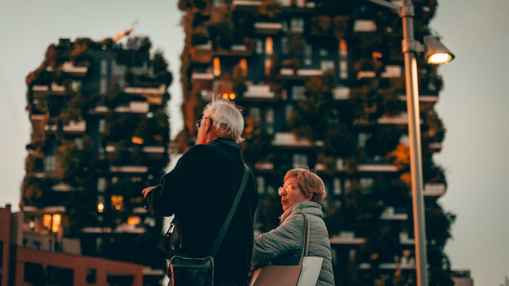 woman and man standing near hand rail with view of high-rise building