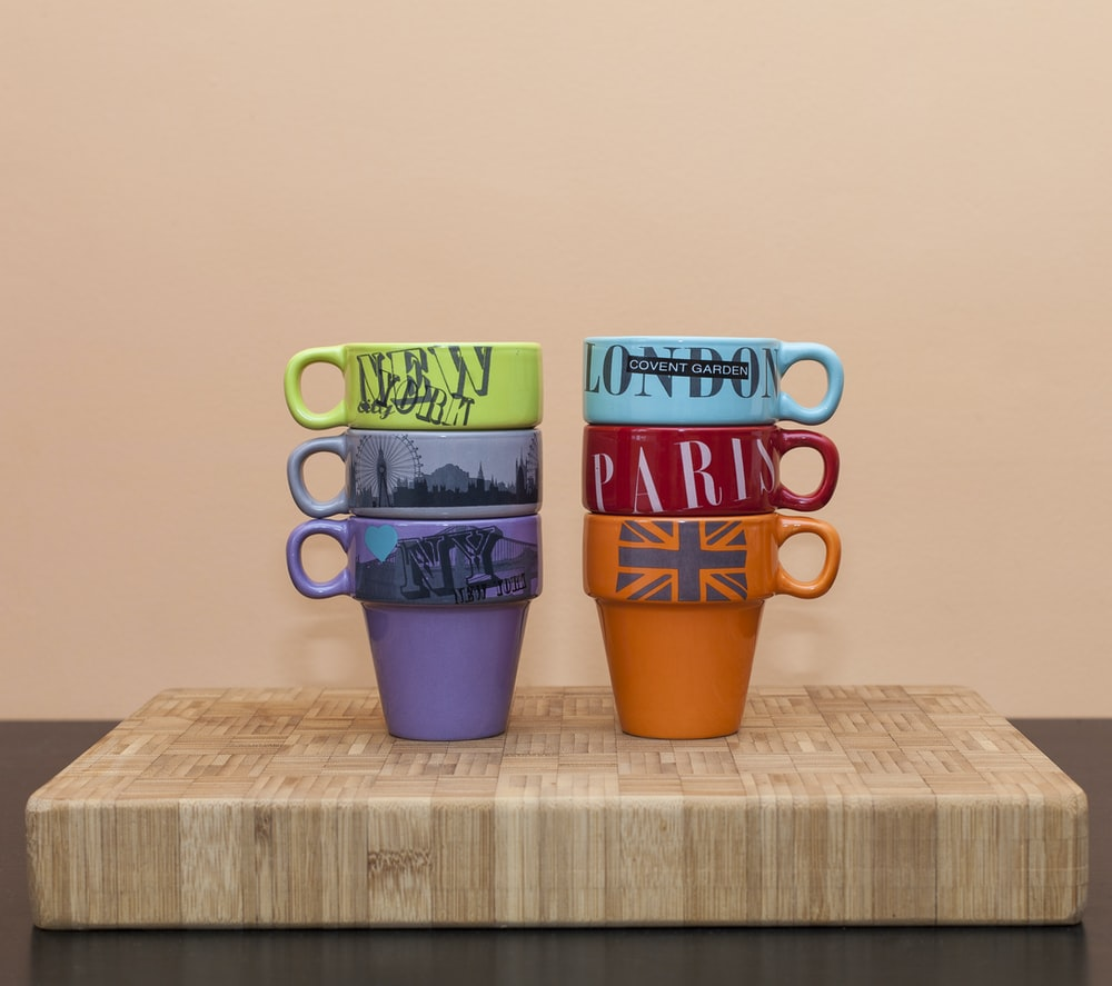 two stacks of six mugs on wooden surface