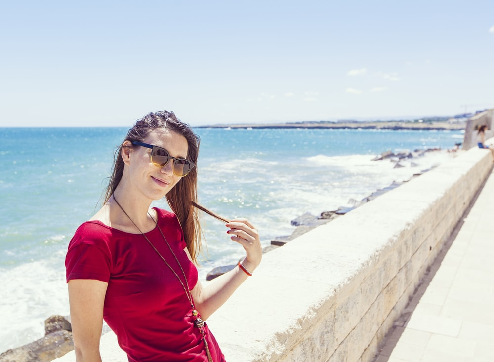 woman smiling and sitting beside concrete railing on island during day