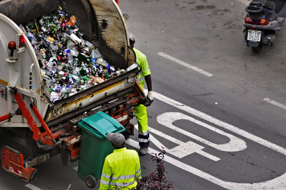 people collecting trash in garbage truck