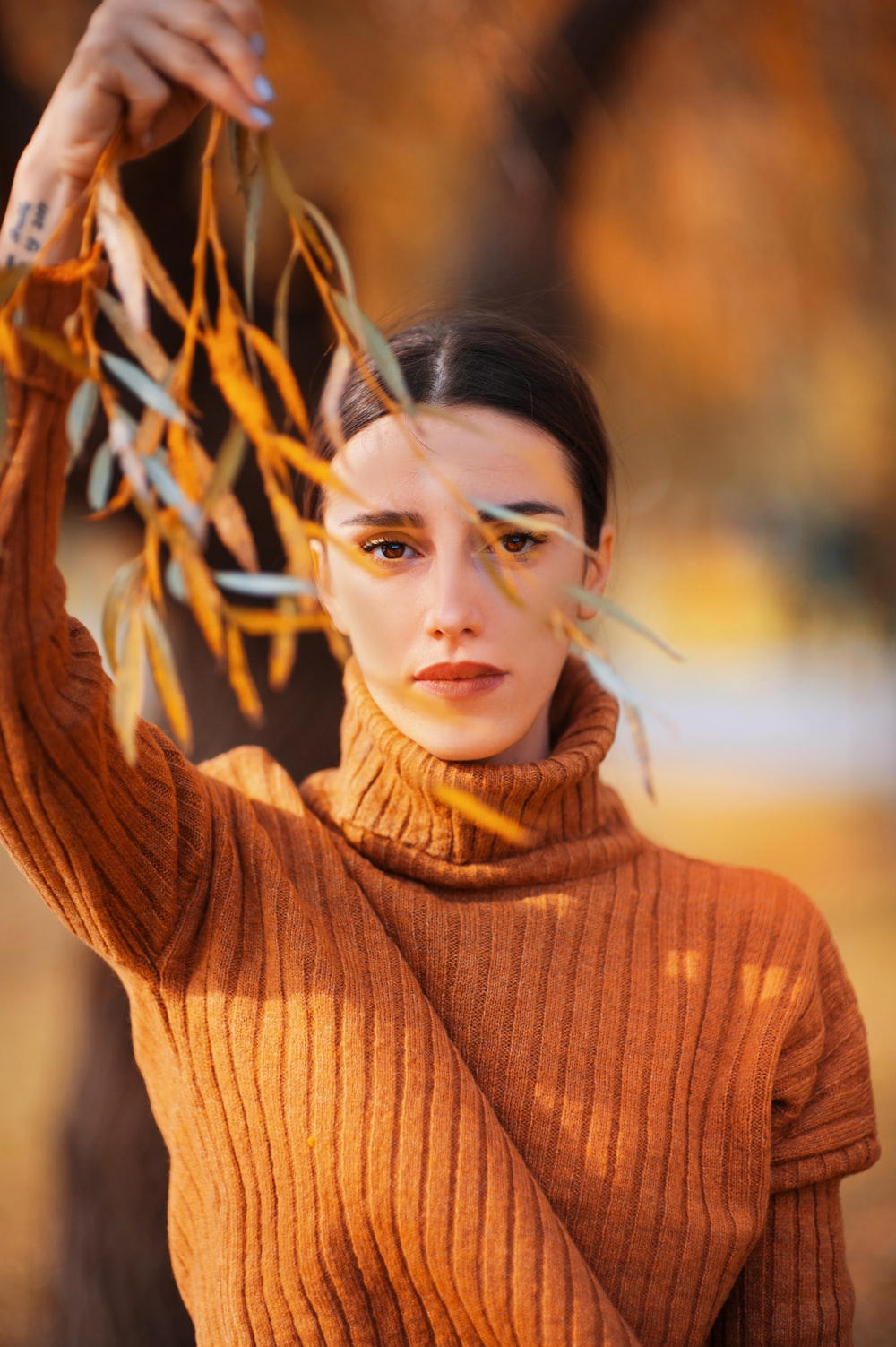 woman in brown turtleneck sweater holding tree leaves