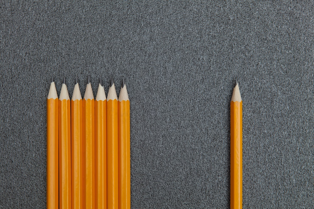 seven orange pencils beside pencil on gray surface