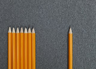 seven orange pencils beside pencil on gray surface
