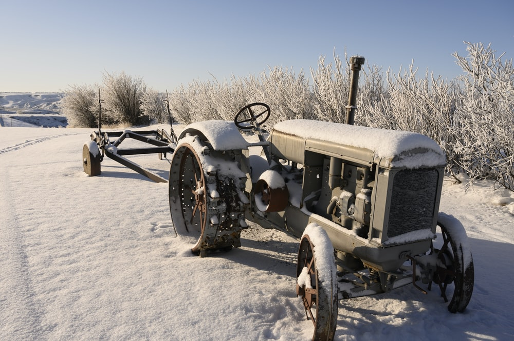 grey tractor covered with snow
