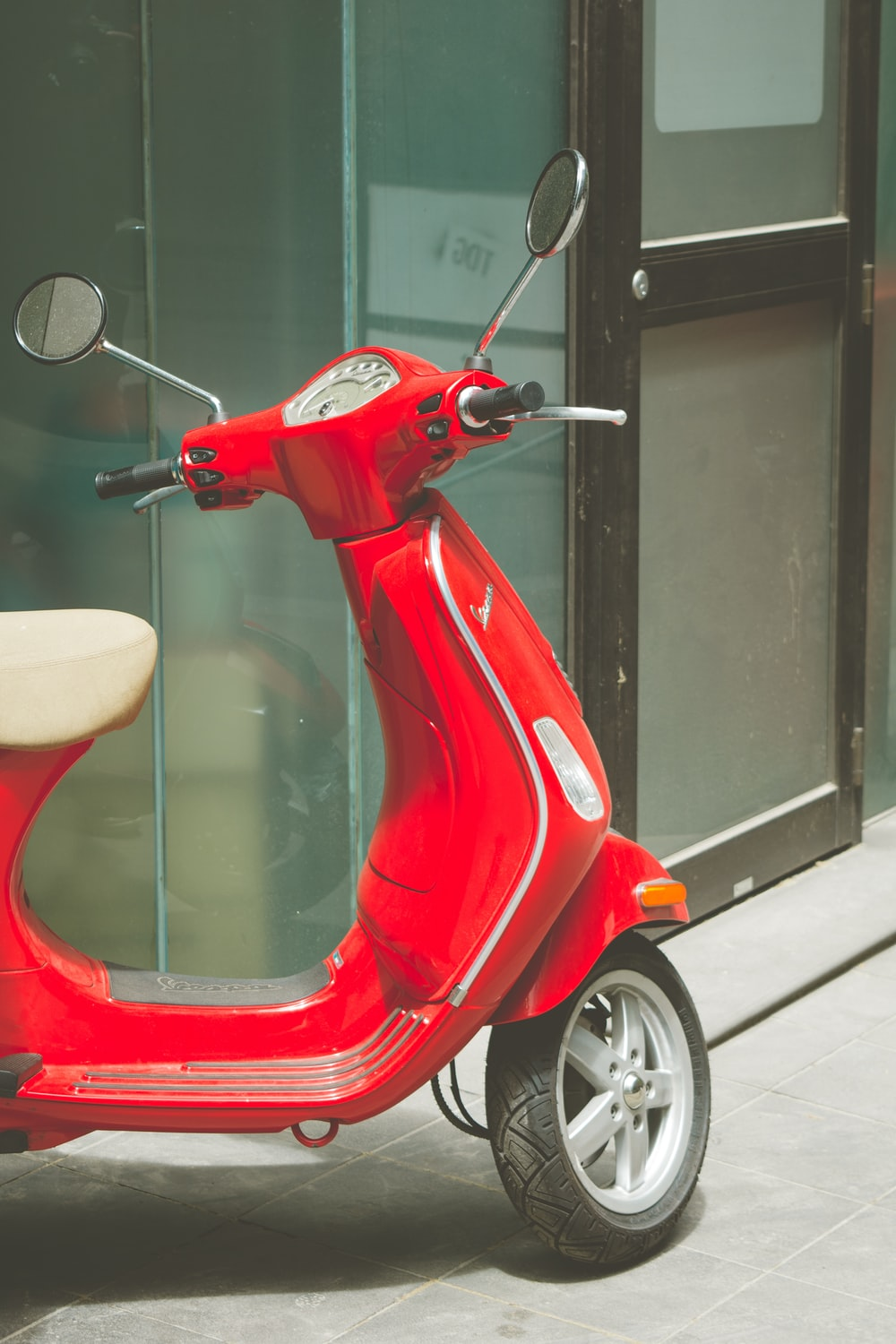 red and white motor scooter beside glass wall