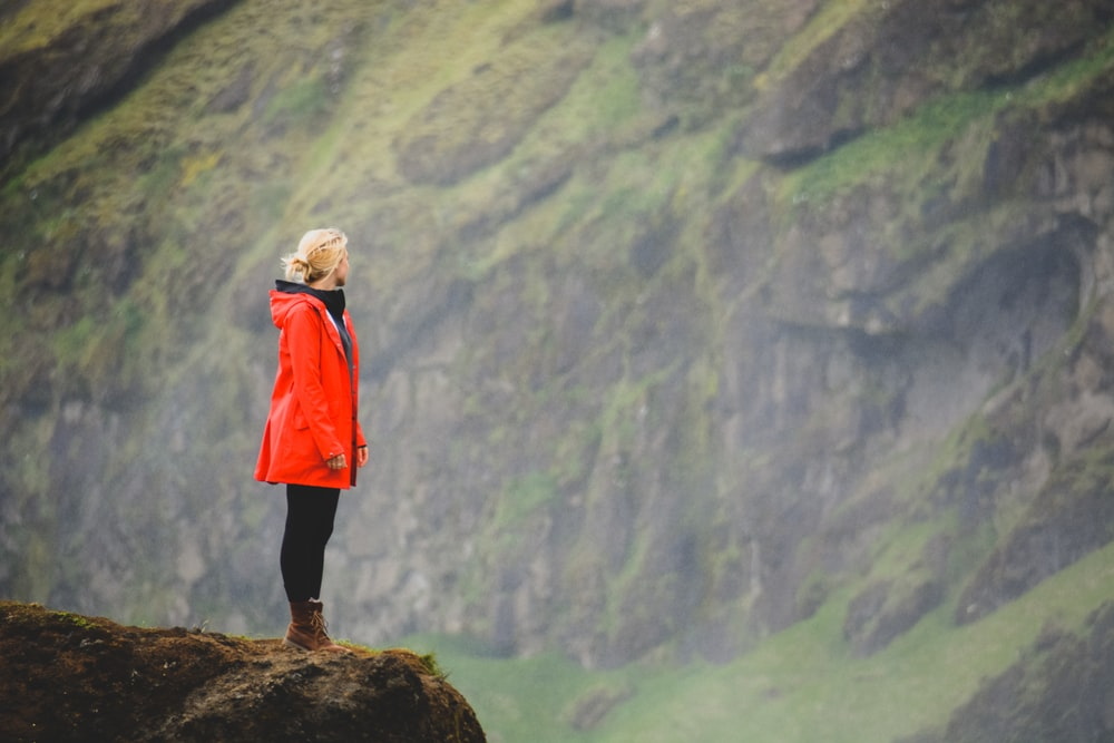 woman in orange parka standing on rock facing cliff